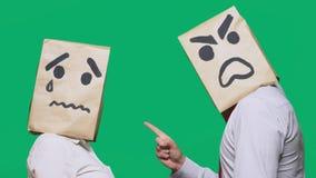 Il concetto delle emozioni e dei gesti Due persone in sacchi di carta con gli smiley Lo smiley aggressivo giura Secondo gridare fotografia stock