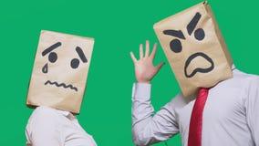 Il concetto delle emozioni e dei gesti Due persone in sacchi di carta con gli smiley Lo smiley aggressivo giura Secondo gridare immagini stock