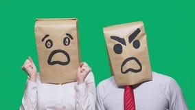 Il concetto delle emozioni e dei gesti Due persone in sacchi di carta con i sorrisi Lo smiley aggressivo giura  fotografia stock libera da diritti