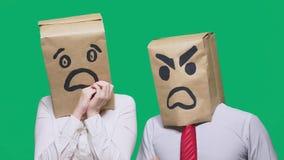 Il concetto delle emozioni e dei gesti Due persone in sacchi di carta con i sorrisi Lo smiley aggressivo giura  immagine stock libera da diritti