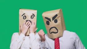 Il concetto delle emozioni e dei gesti Due persone in sacchi di carta con i sorrisi Lo smiley aggressivo giura  fotografie stock