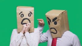 Il concetto delle emozioni e dei gesti Due persone in sacchi di carta con i sorrisi Lo smiley aggressivo giura  immagini stock