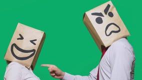 Il concetto delle emozioni e dei gesti Due persone in sacchi di carta con i sorrisi Lo smiley aggressivo giura  fotografia stock