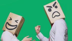 Il concetto delle emozioni e dei gesti Due persone in sacchi di carta con i sorrisi Lo smiley aggressivo giura  fotografie stock libere da diritti