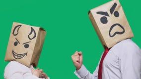 Il concetto delle emozioni e dei gesti Due persone in sacchi di carta con i sorrisi Lo smiley aggressivo giura Secondo diavolo fotografie stock libere da diritti
