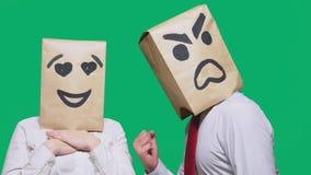Il concetto delle emozioni e dei gesti Due persone in sacchi di carta con un sorriso Lo smiley aggressivo giura Il secondo guarda fotografia stock