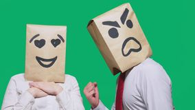 Il concetto delle emozioni e dei gesti Due persone in sacchi di carta con un sorriso Lo smiley aggressivo giura Il secondo guarda immagine stock