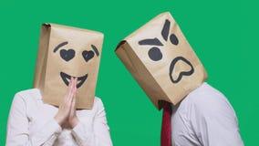 Il concetto delle emozioni e dei gesti Due persone in sacchi di carta con un sorriso Lo smiley aggressivo giura Il secondo guarda immagini stock libere da diritti