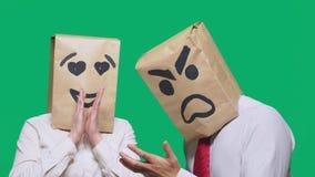 Il concetto delle emozioni e dei gesti Due persone in sacchi di carta con un sorriso Lo smiley aggressivo giura Il secondo guarda fotografia stock libera da diritti