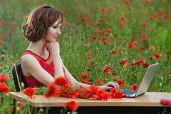 Il concetto di affari ha sparato di bella giovane donna che si siede ad uno scrittorio facendo uso di un computer in un campo Immagini Stock Libere da Diritti