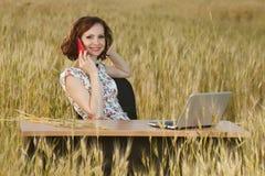 Il concetto di affari ha sparato di bella giovane donna che si siede ad uno scrittorio facendo uso di un computer in un campo Immagini Stock