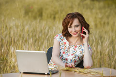 Il concetto di affari ha sparato di bella giovane donna che si siede ad uno scrittorio facendo uso di un computer in un campo Fotografia Stock Libera da Diritti