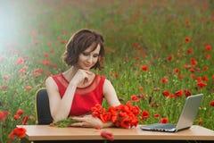 Il concetto di affari ha sparato di bella giovane donna che si siede ad uno scrittorio facendo uso di un computer in un campo Fotografia Stock
