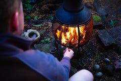 Il concetto di campeggio con all'aperto apre le fiamme del fuoco Fuoco ed uomo di campeggio in foto lunatica crepuscolare scura L Immagine Stock Libera da Diritti