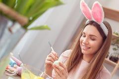 Il concetto di celbration di pasqua della giovane donna a casa in orecchie di un coniglietto che si siedono la coloritura eggs i  fotografia stock libera da diritti