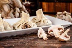 Il concetto di cucina georgiana Khinkali da pasta bianca con i funghi Piatti di servizio in ristorante georgiano su un piatto bia immagine stock libera da diritti