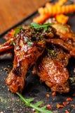 Il concetto di cucina indiana Ali e gambe di pollo al forno in salsa di senape del miele Piatti di servizio nel ristorante sul ne immagini stock libere da diritti