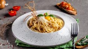 Il concetto di cucina italiana Carbonara della pasta con bacon, parmigiano ed il tuorlo d'uovo La decorazione degli spaghetti fri fotografia stock
