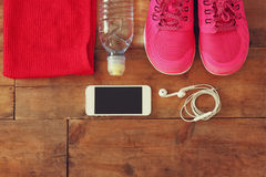 Il concetto di forma fisica con il telefono cellulare con l'asciugamano e la donna mettono in mostra le calzature sopra fondo di  Fotografia Stock