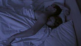 Il concetto di insonnia, i tiri delle coppie nel suo dorme, una vista superiore Lasso di tempo video d archivio