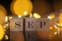 Il concetto di mese, vista frontale mostra il blocco di legno scritto settembre con la l Fotografia Stock