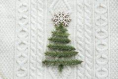 Il concetto di Natale con l'abete rosso, l'abete, fiocchi di neve, su bianco ha tricottato il fondo Scheda di festa Stile dell'an Fotografia Stock