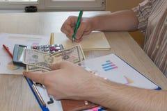 Il concetto di pianificazione finanziaria, risparmio Uomo, soldi con il calcolatore e taccuino sulla tavola di legno La foto most immagine stock libera da diritti