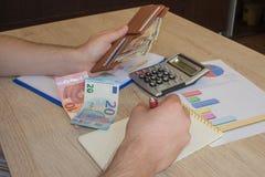Il concetto di pianificazione finanziaria, risparmio Uomo, soldi con il calcolatore e taccuino sulla tavola di legno La foto most fotografie stock libere da diritti