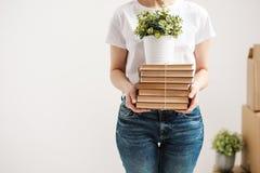 Il concetto di rilocazione e di muoversi verso una nuova casa Il primo piano, mani femminili tiene un mucchio dei libri e di una  immagine stock