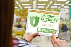 Il concetto di sicurezza di Internet, ragazza tiene la compressa digitale sul fondo vago del negozio fotografie stock libere da diritti