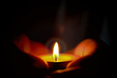 Il concetto di speranza e di preghiera della candela si accende in mani Fotografia Stock