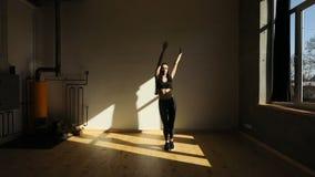 Il concetto di sport della giovane donna che solleva le gambe al petto, pareggiante, saltante e filante sul posto Lo studio archivi video