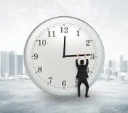 Il concetto di tempo di completamento con l'uomo d'affari che prova a fermare il tempo a Immagini Stock Libere da Diritti