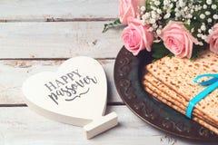Il concetto ebreo di Pesah di pesach di festa con il matzoh, i fiori rosa e la forma del cuore cedono firmando un documento il fo Fotografia Stock