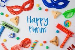 Il concetto ebreo di Purim di festa con hamantaschen i biscotti, la maschera di carnevale ed il noisemaker su fondo bianco Fotografia Stock