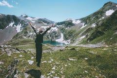 Il concetto emozionale di salto di stile di vita di viaggio delle montagne delle mani sollevato uomo del viaggiatore avventura l' Fotografie Stock