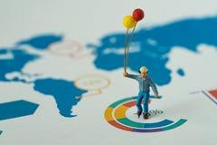 Il concetto felice di affari come tenuta miniatura dell'uomo balloons l'interim Fotografia Stock
