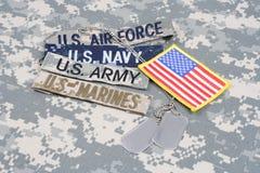 Il concetto MILITARE degli Stati Uniti con nastri adesivi del ramo e le medagliette per cani su cammuffamento uniformano immagini stock libere da diritti