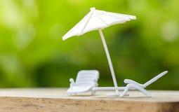 Il concetto o il piano di assicurazione di vendite si rilassa sull'ombrello di festa che protegge sulla sedia del banco per la fa immagine stock