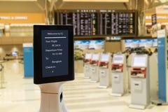 Il concetto robot astuto della tecnologia, il passeggero segue un robot di servizio ad un contro controlla in aeroporto, il robot Immagine Stock Libera da Diritti