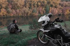 Il concetto solo, uomo sta sedendosi da solo e sguardo alla distanza Il motociclo di avventura, motociclista, un driver della mot fotografia stock libera da diritti