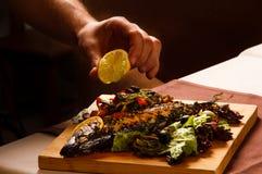 Il condimento ha appoggiato il pesce con le verdure con il succo di limone Fotografie Stock