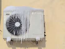 Il condizionatore coperto di ghiaccioli su una parete gialla fotografia stock