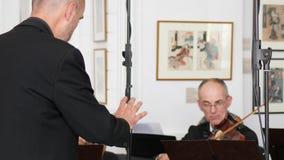 Il conduttore di un'orchestra dirige i musicisti con i movimenti delle sue mani stock footage