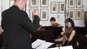 Il conduttore sta vicino al supporto con le note musicali sui violinisti del fondo alla sala da concerto video d archivio