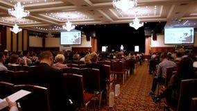 Il conferenziere dice e mostra la presentazione o la conferenza sulla scena alla casa imballata degli ascoltatori video d archivio