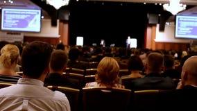 Il conferenziere dice e mostra la presentazione o la conferenza sulla scena alla casa imballata degli ascoltatori, la folla non a video d archivio