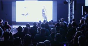 Il conferenziere dice e mostra la presentazione sullo schermo proiettivo alla casa imballata degli ascoltatori video d archivio