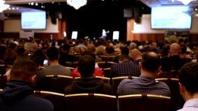 Il conferenziere dice la presentazione sulla scena alla casa imballata degli ascoltatori stock footage