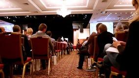 Il conferenziere mostra la presentazione o la conferenza sulla scena alla casa imballata degli ascoltatori, la folla non a fuoco video d archivio